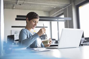 Businesswoman in office having lunch break - RBF05262