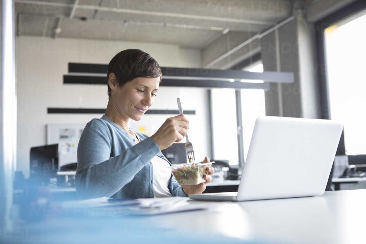 Businesswoman in office having lunch break - RBF05262 - Rainer Berg/Westend61