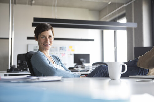 Portrait of smiling businesswoman in office - RBF05265