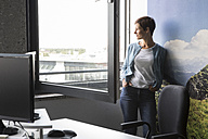 Businesswoman in office looking out of window - RBF05271