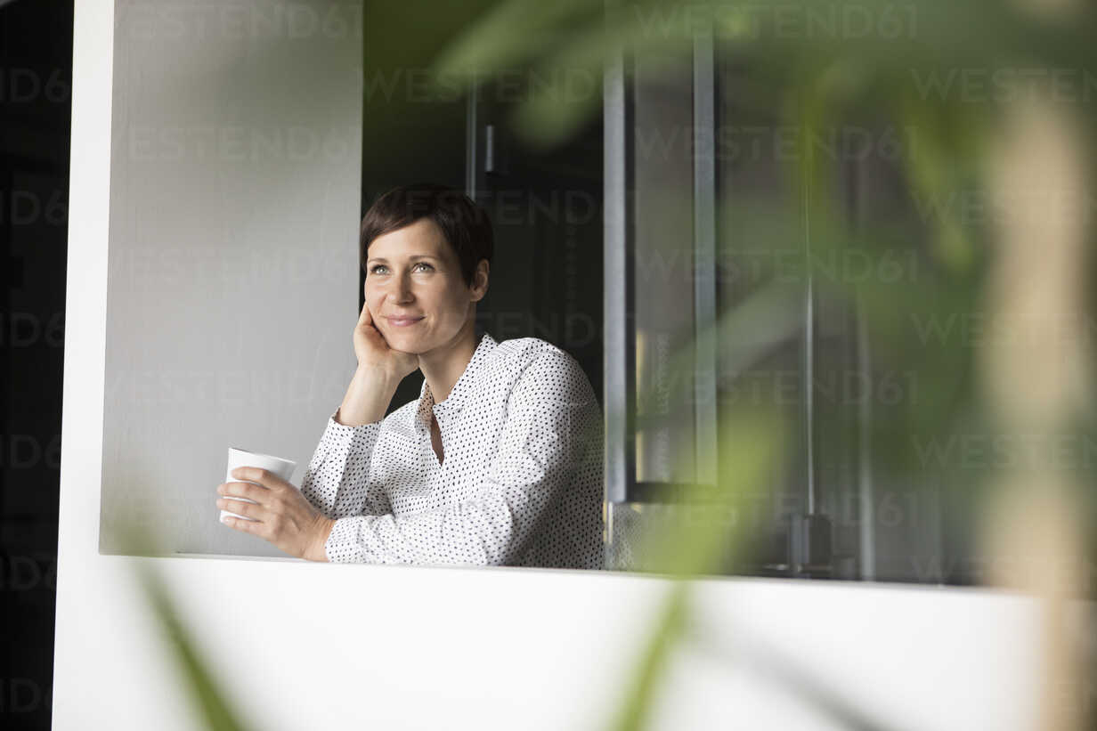 Smiling woman with cup of coffee at the window - RBF05274 - Rainer Berg/Westend61