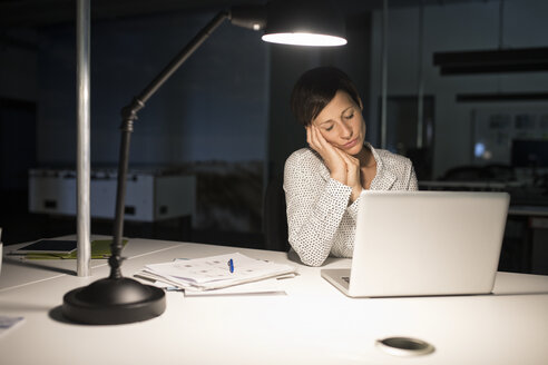 Exhausted businesswoman in office with laptop in the dark - RBF05277