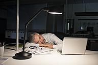 Exhausted businessman sleeping on office desk - RBF05280