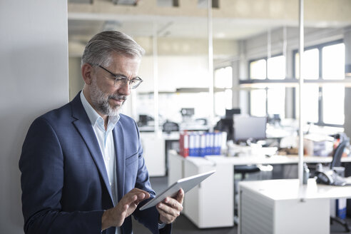 Businessman in office using tablet - RBF05292