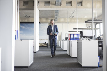 Businessman walking in office holding documents - RBF05298