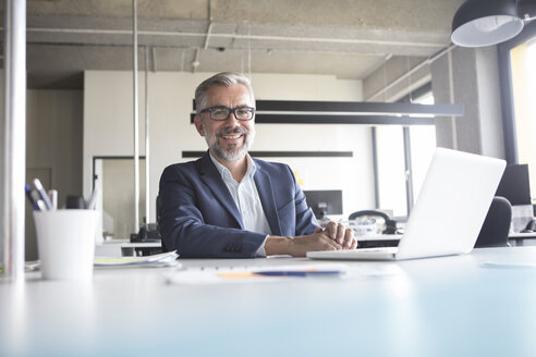 Smiling businessman using laptop in office - RBF05304