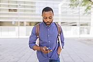 Man with backpack looking at his cell phone - GIOF01683