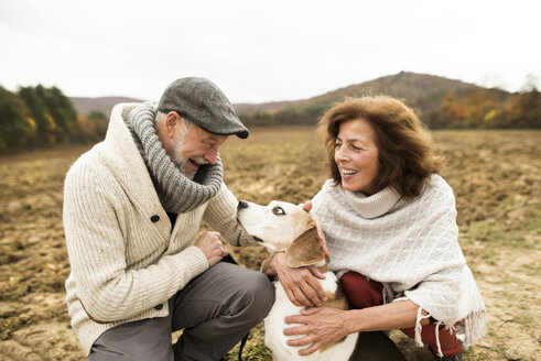 Happy senior couple with dog in nature - HAPF01153