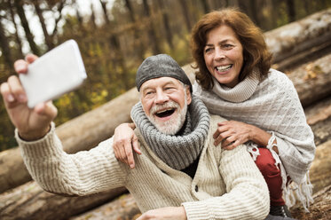 Portrait of laughing senior couple taking selfie with cell phone - HAPF01162