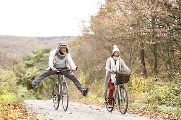 Senior couple doing a bicycle trip with dog in autumn - HAPF01174