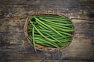 Wickerbasket of green beans on dark wood - LVF05640