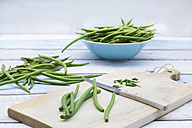 Green beans, wooden board and kitchen knife on wood - LVF05646