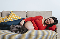 Happy pregnant woman lying on the couch with her cat - GEMF01299