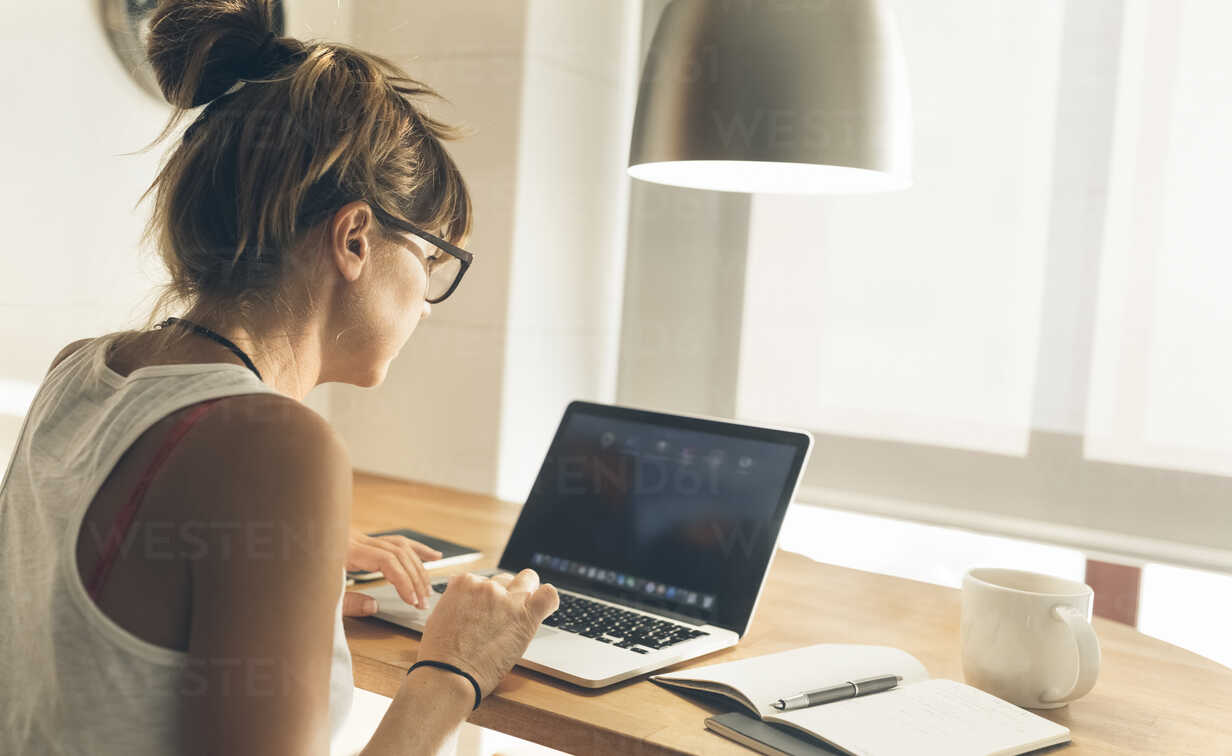 Woman using laptop at desk - MGOF02664 - Marco Govel/Westend61