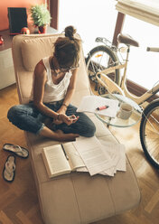 Woman at home with cell phone working on script - MGOF02667