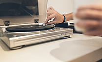 Woman putting on an old vinyl record at home - MGOF02676