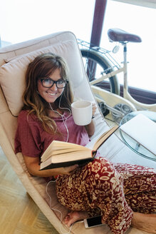 Smiling woman reading a book at home - MGOF02679