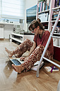 Woman at home sitting on floor using laptop - MGOF02682