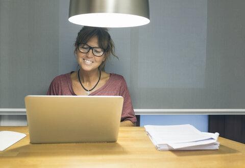 Smiling woman using laptop at desk - MGOF02685