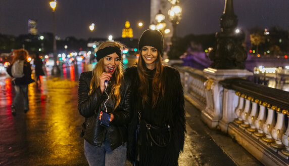 France, Paris, two young women walking on a bridge over the Seine River - MGOF02690