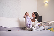 Mother holding up baby girl at home - SIPF01153