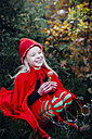 Little imp sitting in forest, holding fly agaric - MJF02108