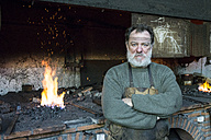 Portrait of confident blacksmith in his workshop - ABZF01588