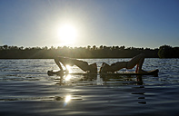 Two women doing yoga on paddleboard at sunset - FMKF03271