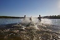 Playful friends splashing in a lake - FMKF03280