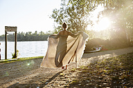 Young woman holding a blanket at a lake at sunset - FMKF03295