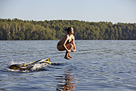 Woman jumping into water from paddleboard - FMKF03301