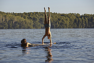 Man doing a handstand on a paddleboard in a lake - FMKF03304