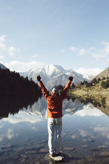 France, Pyrenees, Pic Carlit, hiker raising his arms at mountain lake - KKAF00164