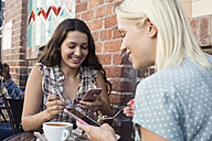Two young women using cell phones at outdoor cafe - WEST22142