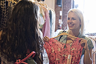 Happy young woman shopping for new clothes with friend - WEST22148