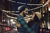 Happy young couple hugging on the steet at night - WEST22154