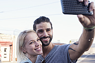 Happy young man with girlfriend taking a selfie - WEST22160