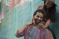 Happy young couple with cell phone outdoors - WEST22190