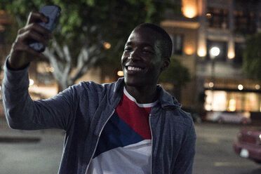 Smiling young man taking a selfie at night - WEST22196