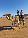 Oman, Al Raka, Rimal Al Wahiba desert, two women riding on dromedaries - AMF05123