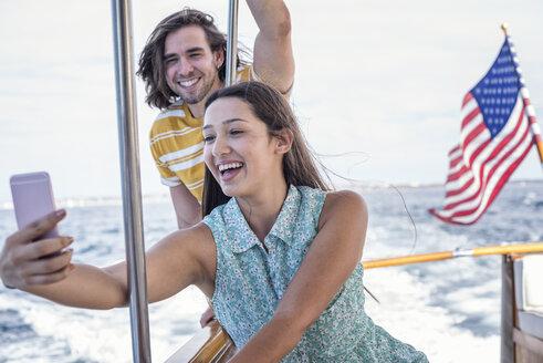 Happy couple on a boat trip taking a selfie - WESTF22214