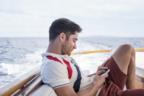 Young man on a boat trip looking at cell phone - WESTF22247