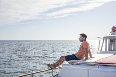 Young man sitting on a boat - WESTF22256