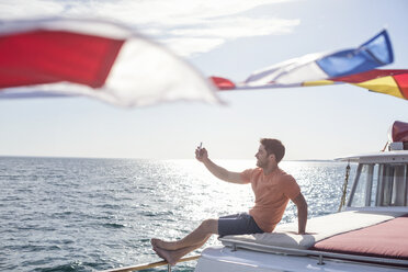 Young man sitting on a boat taking a selfie - WESTF22262