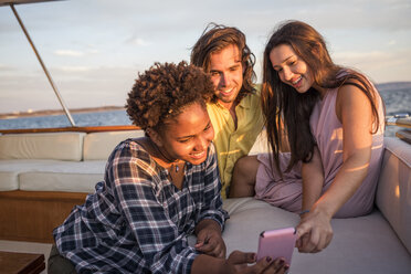 Friends on a boat trip with cell phone - WESTF22280