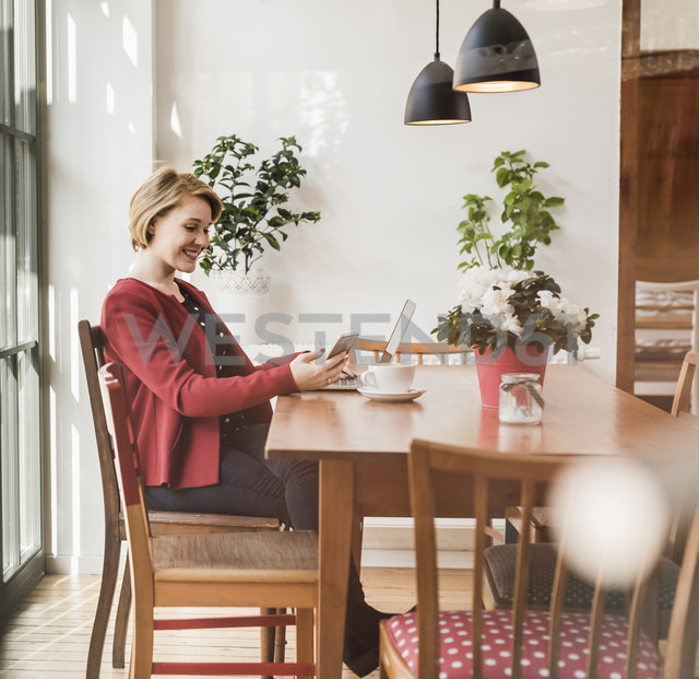 Smiling young woman with cell phone and laptop in a cafe - UUF09432 - Uwe Umstätter/Westend61