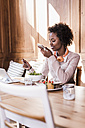 Young woman using cell phone and tablet in a cafe - UUF09468