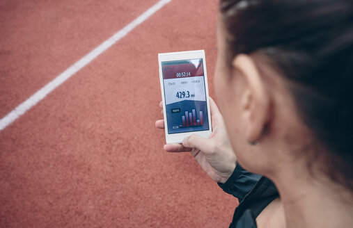 Athlete looking on smartphone with training data on display - DAPF00500