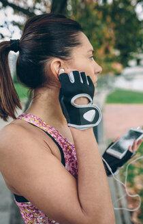 Female athlete applying earbuds - DAPF00509