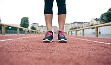 Woman standing on tartan track - DAPF00518